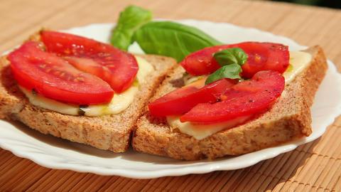 Sandwich, bread pesto mozzarella tomato and basil Stock Video Footage