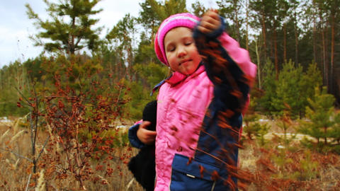 Little girl walking and playing outdoor in the aut Stock Video Footage