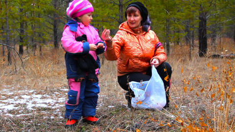 Young women with daughter picking up plant leaves Stock Video Footage