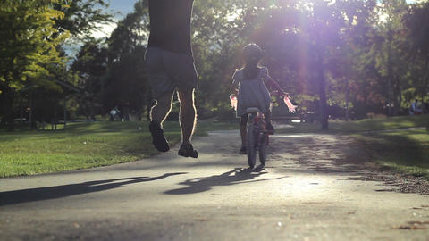 Excited Father Helps Daughter Ride Bike For First stock footage