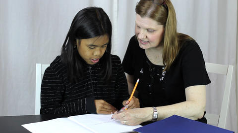 Mother Helps Asian Daughter With Homework Stock Video Footage