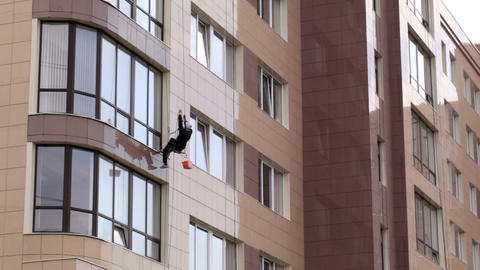 Man washes the windows of office building 1 Stock Video Footage