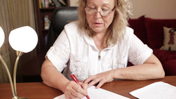 Middle-aged woman writing at the table Stock Video Footage