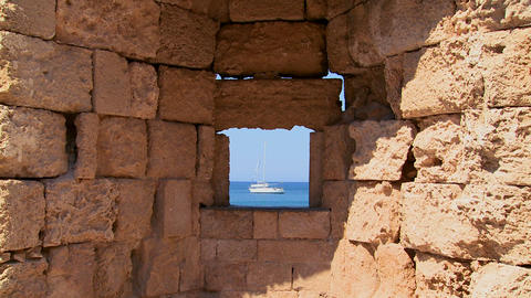 A sailboat is perfectly framed through a castle wa Stock Video Footage