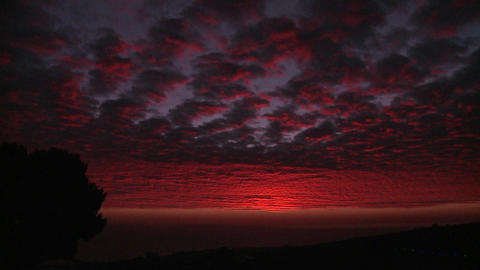 A gorgeous deep crimson sun sets behind the Channe Stock Video Footage