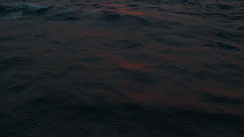 Red sunset light reflects off ocean waves Footage
