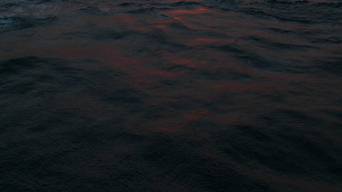 Red sunset light reflects off ocean waves Stock Video Footage