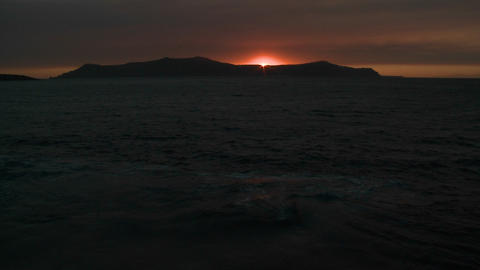 The sun sets behind an island in the ocean Footage