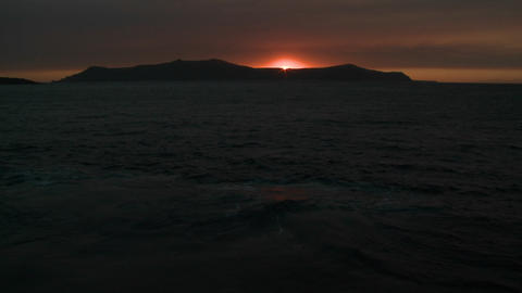 The sun sets behind an island in the ocean Stock Video Footage