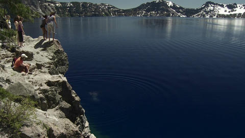 People jump into the waters of Crater Lake, Oregon Stock Video Footage