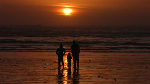 A family stands on the beach silhouetted against t Footage