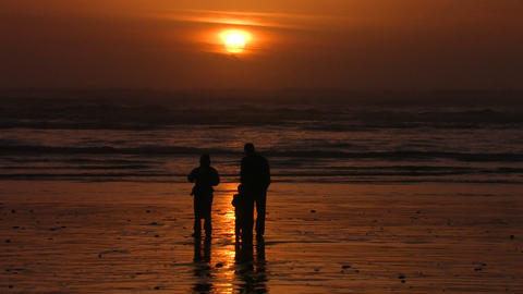 A family stands on the beach silhouetted against t Stock Video Footage