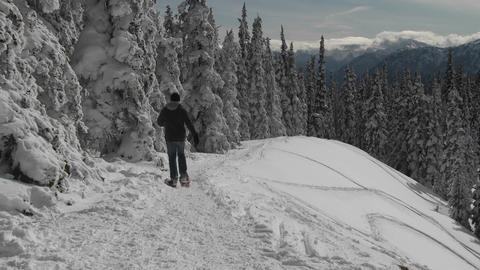 A man snowshoes across a snowy mountainside Footage