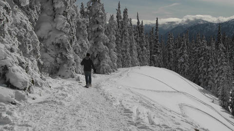 A man snowshoes across a snowy mountainside Stock Video Footage