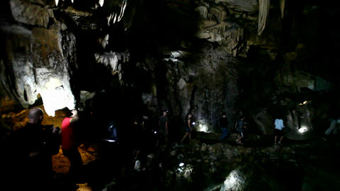 People explore a dark cave with flashlights Footage