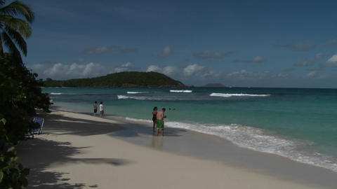 People stroll along an island beach in the Caribbe Footage