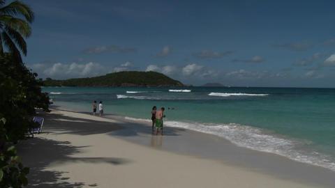 People stroll along an island beach in the Caribbe Footage