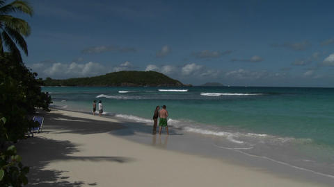 People stroll along an island beach in the Caribbe Stock Video Footage