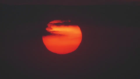 The sun slowly sets through the clouds in a huge o Stock Video Footage