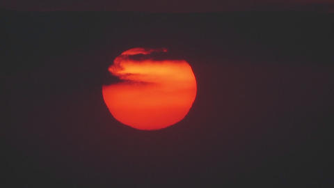 The sun slowly sets through the clouds in a huge o Footage