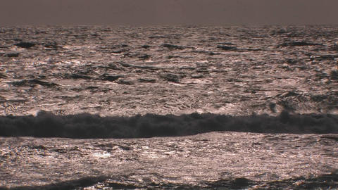 Choppy waves continuously break and roll onto shor Footage