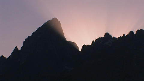 A silhouette of a mountainside with the sun settin Footage