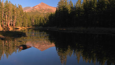 A mountain lake reflects the surrounding trees at Stock Video Footage