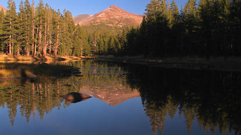 A mountain lake reflects the surrounding trees at  Footage