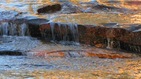 Water flows over flat rocks at Tuolumne Meadows in Footage
