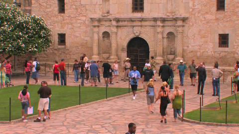 People walk around a stone courtyard and building Stock Video Footage