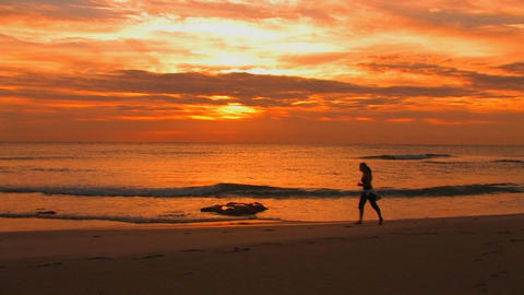 A woman jogs on the beach during golden-hour Footage