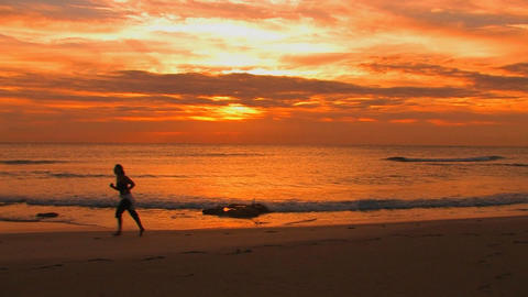 A woman jogs on the beach during golden-hour Stock Video Footage