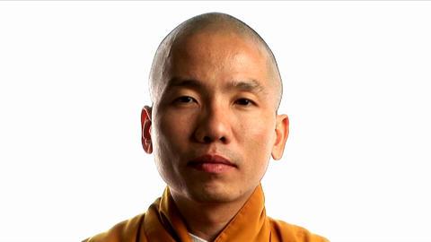 A Buddhist monk wearing an orange robe Footage