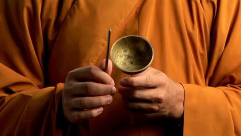 A Buddhist monk wearing an orange robe taps a bell Footage