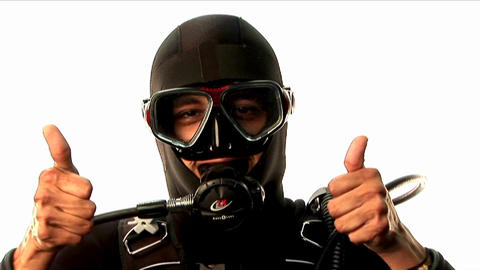 A scuba diver gives two thumbs up on land Live Action