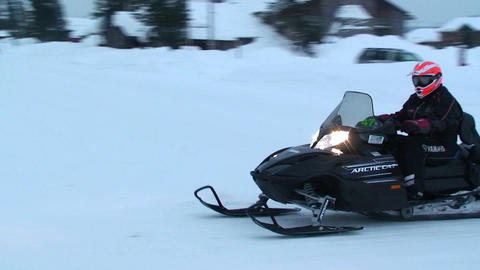 A snowmobile rides his snowmobile through a town Stock Video Footage