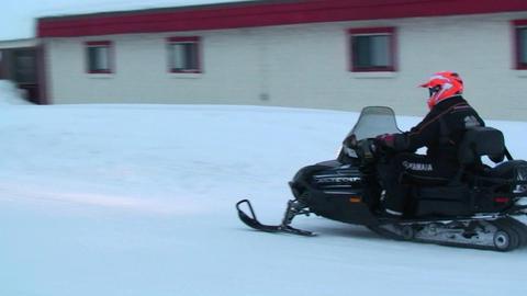 A snowmobile rides his snowmobile through a town Footage