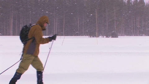 A cross country skier moves across a snowy landsca Footage