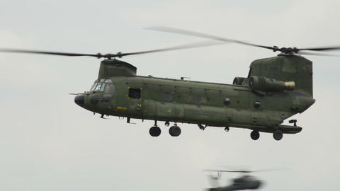 Chinook CH 47 Helicopter fly by Apache background Stock Video Footage