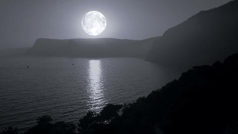 Big moon illuminates the mountains and the sea Stock Video Footage