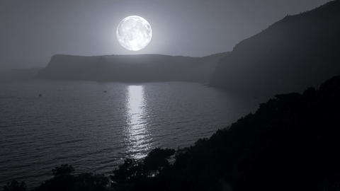 Big moon illuminates the mountains and the sea Stock Video Footage