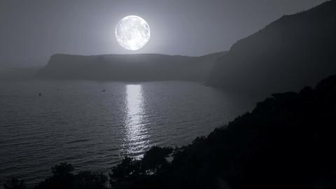 Big moon illuminates the mountains and the sea Footage