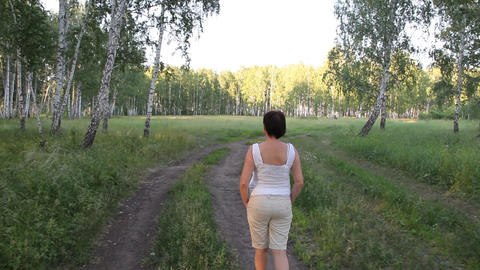Woman walking on the road along the forest Stock Video Footage