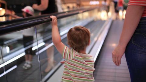 Little boy rises on the escalator Stock Video Footage