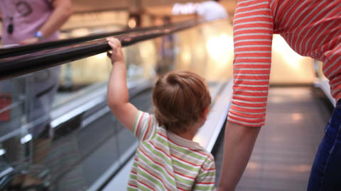 Little boy rises on the escalator Stock Video Footage
