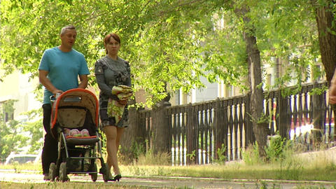 Parents are walking with a stroller Stock Video Footage