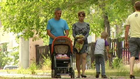 Parents are walking with a stroller Footage