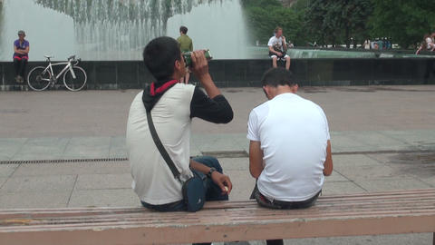 Two guys on the bench by the fountain Stock Video Footage