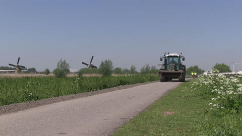 Tractor and windmills in The Netherlands Stock Video Footage