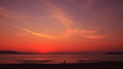 People go along the seashore at sunrise Stock Video Footage